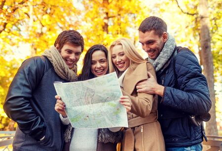 hugging couple: travel, vacation, people, tourism and friendship concept - group of smiling friends looking to map in city park