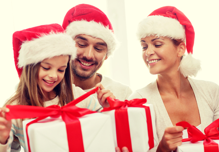 family holidays: family, happiness, generation, holidays and people concept - happy family in santa helper hats with gift boxes sitting on couch at home Stock Photo