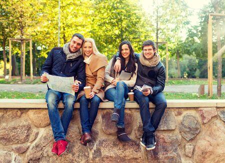 grupo de amigos sonrientes que se sientan con el mapa de la tableta de ordenador PC y bebidas calientes en el parque