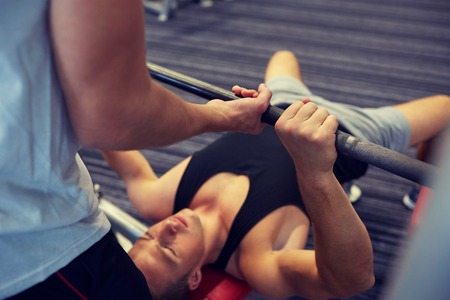 barbell: young man and personal trainer with barbell flexing muscles in gym