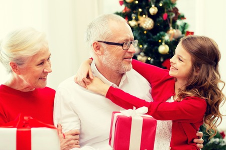 smiling grandparents and granddaughter with gift boxes sitting on couch at home
