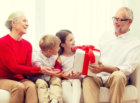 birthday present: smiling grandparents and grandchildren with gift box sitting on couch at home