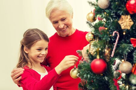 home decorating: smiling girl with grandmother decorating christmas tree at home
