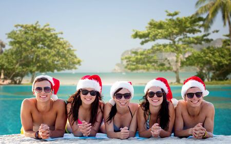 christmas hat: group of friends in santa helper hats on beach Stock Photo