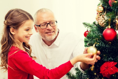 home decorating: smiling girl with grandfather decorating christmas tree at home Stock Photo