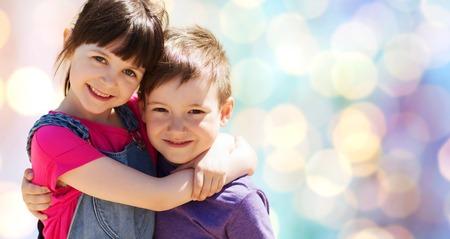 best friend: two happy kids hugging over blue lights background