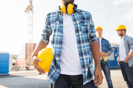 close up of builder holding yellow hardhat or helmet outdoors