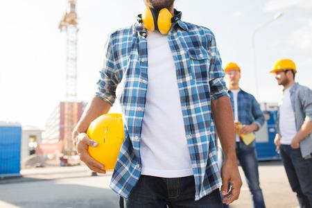 close-up van de bouwer met gele bouwvakker of helm buitenshuis