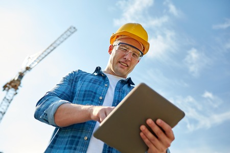 smiling builder in hardhat with tablet pc computer over group of builders at construction site Reklamní fotografie