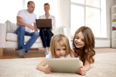 niños jugando videojuegos: niñas felices jugando con el ordenador Tablet PC en el hogar