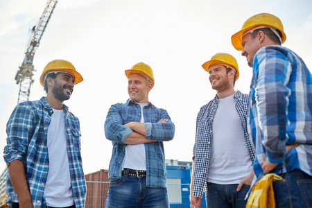 happy worker: group of smiling builders in hardhats at construction site Stock Photo