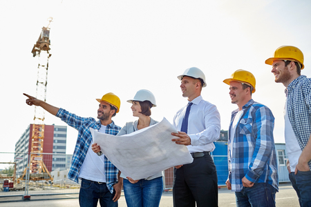 site construction: group of builders and architects in hardhats with blueprint on construction site Stock Photo