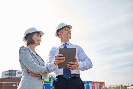 lächelnd Mann und Frau in Schutzhelmen mit Tablet-PC-Computer auf der Baustelle