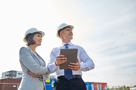 smiling man and woman in hardhats with tablet pc computer at construction site