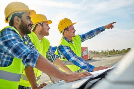 close up of builders in hardhats and high visible vests with blueprint on car hood