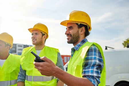 visible: happy male builders in high visible vests with walkie talkie or radio outdoors