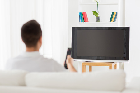 man watching tv and changing channels at home from back