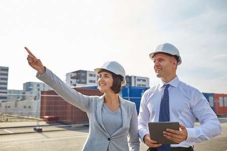 developers: smiling man and woman in hardhats with tablet pc computer pointing finger up at construction site Stock Photo