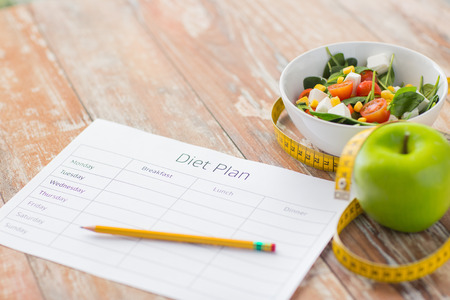 diet plan: close up of diet plan paper green apple, measuring tape and salad