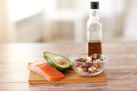 close up of salmon fillets, avocado, olive oil bottle and nuts in glass bowl on table