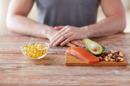 fish oil: close up of male hands with food rich in protein on cutting board on table