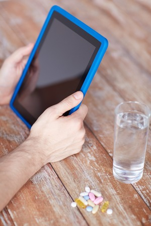 animal body part: close up of male hands with tablet pc computer, pills and water on table Stock Photo
