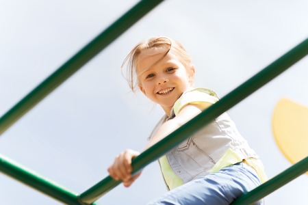climbing frame: happy little girl on children playground climbing frame