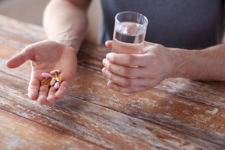 acqua bicchiere: close up of male hands holding pills with cod liver oil capsules and water glass