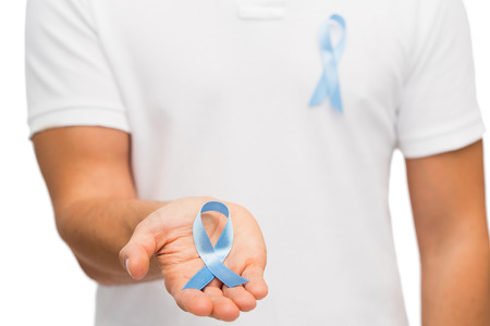 medicine, health care, gesture and people concept - close up of male hand holding blue prostate cancer awareness ribbon