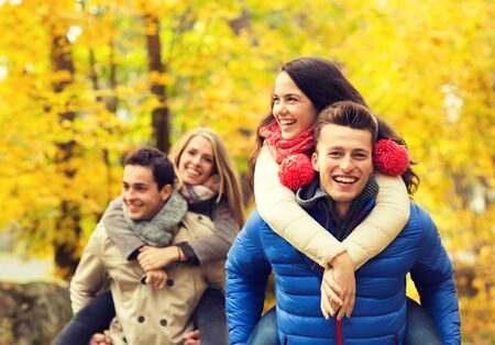 love and friendship: love, friendship, family and people concept - smiling friends having fun in autumn park