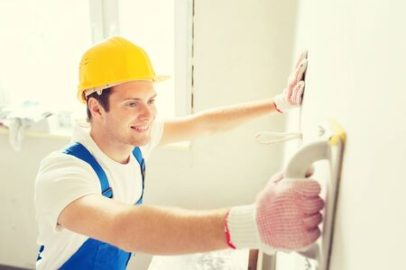 business tool: business, building, profession and people concept - smiling builder with grinding tool indoors