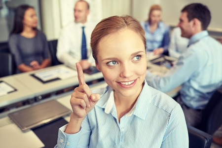 woman pointing up: business, people and teamwork concept - smiling businesswoman pointing finger up with group of businesspeople meeting in office