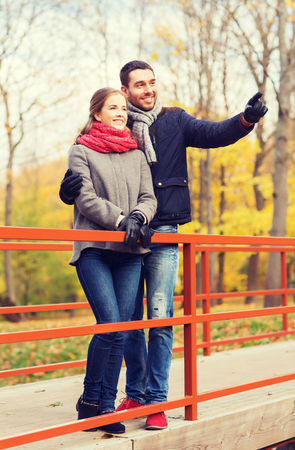 hombres guapos: love, gesture, family, season and people concept - smiling couple hugging on bridge in autumn park Foto de archivo