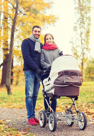 baby love: love, parenthood, family, season and people concept - smiling couple with baby pram in autumn park