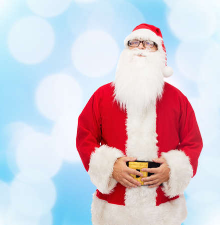 christmas costume: christmas, holidays and people concept - man in costume of santa claus over blue lights background