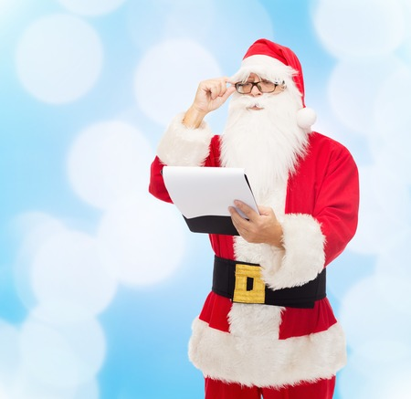 christmas costume: christmas, holidays and people concept - man in costume of santa claus with notepad over blue lights background