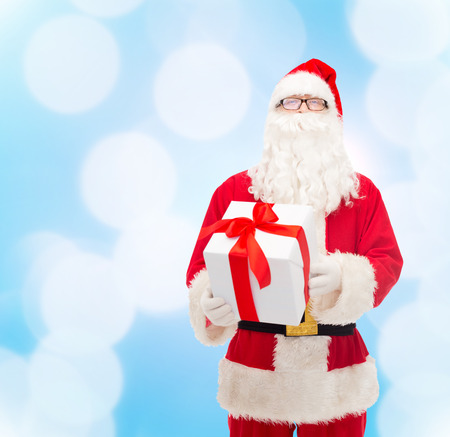 christmas costume: christmas, holidays and people concept - man in costume of santa claus with gift box over blue lights background Stock Photo