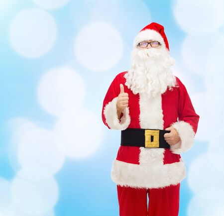 christmas costume: christmas, holidays, gesture and people concept- man in costume of santa claus showing thumbs up over blue lights background Stock Photo