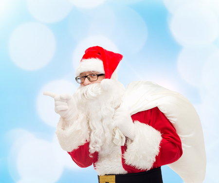 nicolas: christmas, holidays and people concept - man in costume of santa claus with bag pointing finger over blue lights background