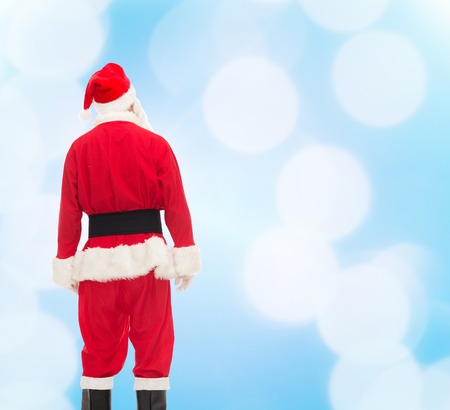 christmas costume: christmas, holidays and people concept - man in costume of santa claus from back over blue lights background Stock Photo