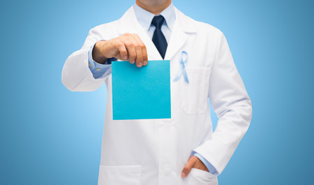 urologist: healthcare, advertisement, people and medicine concept - close up of male doctor in white coat with sky blue prostate cancer awareness ribbon holding blank paper