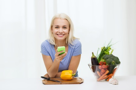 healthy smile: healthy eating, vegetarian food, dieting and people concept - smiling young woman with smartphone cooking vegetables at home Stock Photo