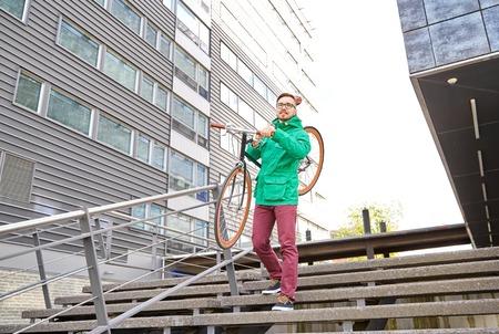 down the stairs: la gente, el deporte, el estilo, el ocio y estilo de vida - hombre joven que lleva inconformista bicicleta fija del engranaje en el hombro por las escaleras en la ciudad