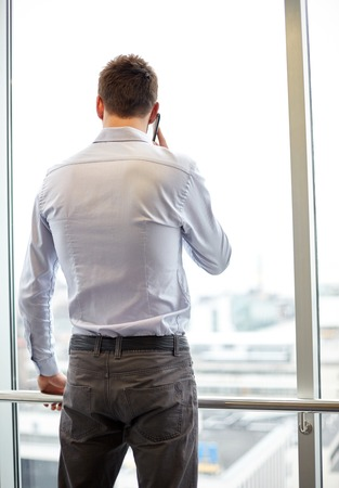 looking out: business, technology and people concept - businessman calling on smartphone and looking out office window