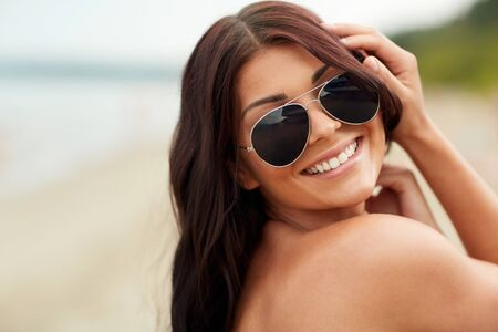 hispanic girl: summer vacation, tourism, travel, holidays and people concept -face of smiling young woman with sunglasses on beach Stock Photo