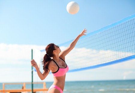 beach volley: summer vacation, sport and people concept - young woman with ball playing volleyball on beach Stock Photo