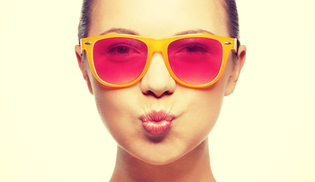 sunglasses: love, happiness, valentines day, face expressions and people concept - portrait of teenage girl in pink sunglasses blowing kiss Stock Photo