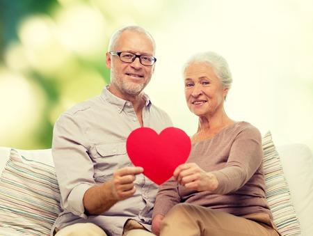 Familie, Urlaub, Alter und Menschen Konzept - glücklich Senior Paar hält kleine rote Papier Herzform Ausschnitt und sitzt auf Sofa über grünem Hintergrund
