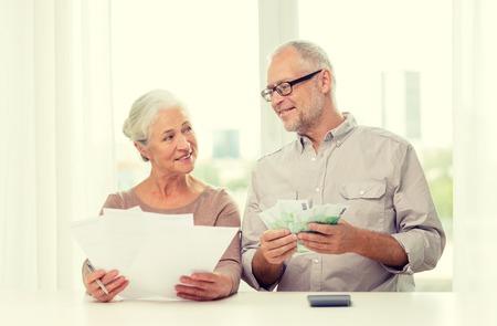 Familie, Ersparnisse, Alter und Personen-Konzept - lächelnde ältere Paare mit Papieren, Geld und Taschenrechner zu Hause