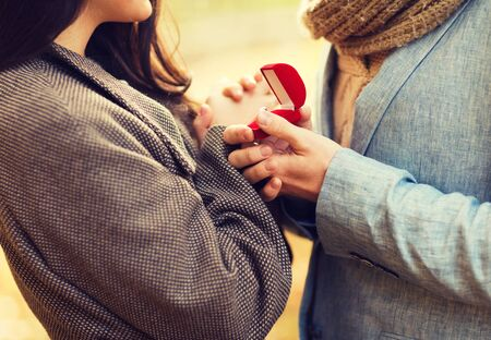 part of me: love, relationship, family and people concept - close up of couple with red gift box in autumn park Foto de archivo